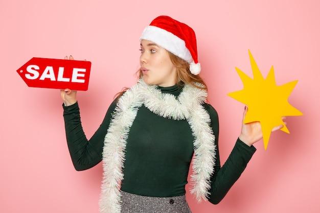 Vorderansicht junge frau, die große gelbe figur und verkaufsschreiben auf rosa wandfarbmodellmodellfeiertags-neujahrsemotion hält
