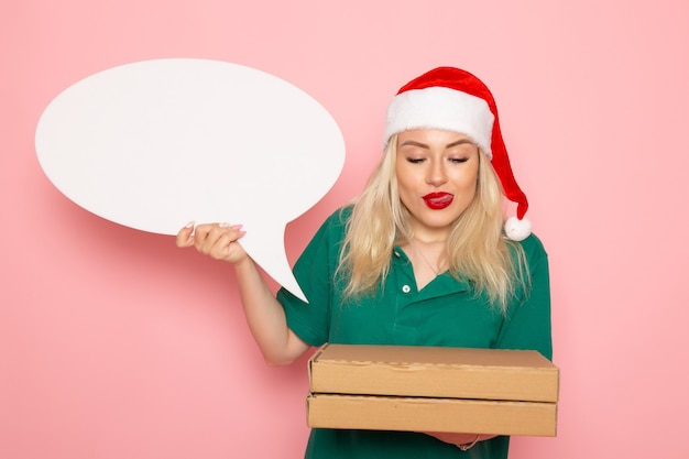 Vorderansicht junge frau, die großes weißes schild und lebensmittelboxen auf rosa wandfotoarbeit neujahrsferienjob-kurieruniform hält