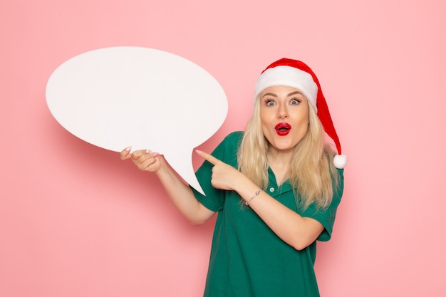 Vorderansicht junge frau, die großes weißes zeichen auf der rosa wandfrau schneefarbfoto neujahrsfeiertag hält