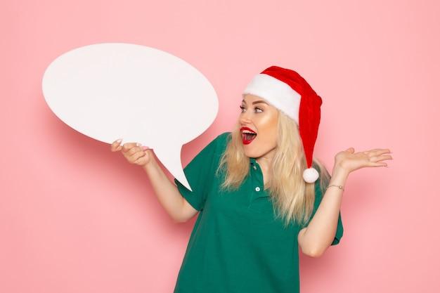 Vorderansicht junge frau, die großes weißes zeichen auf rosa wandfrau beschenkt schneefarbenfoto neujahrsfeiertag