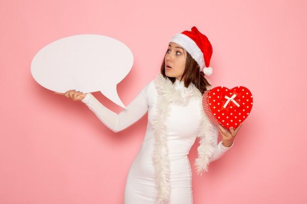 Vorderansicht junge frau, die großes weißes zeichen hält und auf rosa wandemotionsfarbe schneeweihnachts-neujahrsfeiertag präsentiert