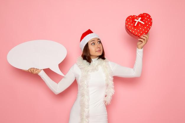 Vorderansicht junge frau, die großes weißes zeichen hält und auf rosa wandfarbe schnee weihnachten neujahr emotionen urlaub präsentiert