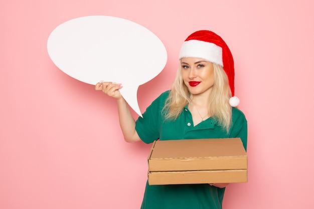 Vorderansicht junge frau, die großes weißes zeichen und nahrungsmittelkästen auf rosa wandfotoarbeitsuniform neujahrsferienjobkurier hält
