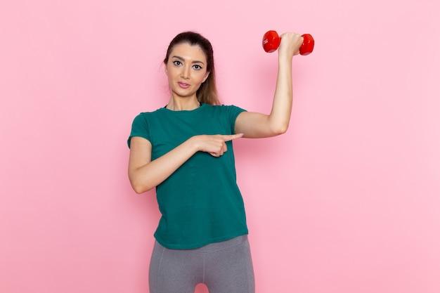 Vorderansicht junge frau, die hanteln auf den hellrosa wandathleten-sportübungsgesundheitsübungen hält