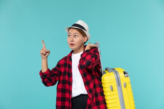 Vorderansicht junge frau, die in den urlaub mit ihrer gelben tasche auf dem blauen raum geht