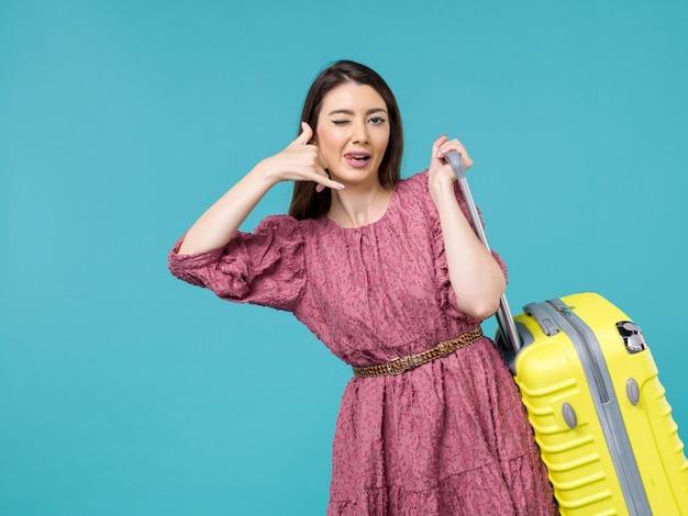 Vorderansicht junge frau, die in den urlaub mit ihrer gelben tasche auf hellblauer hintergrundreise sommerreisefrau menschliches meer geht