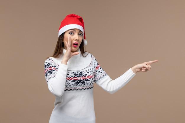Vorderansicht junge frau, die in der roten kappe auf braunem hintergrund emotionen weihnachten neujahr aufwirft
