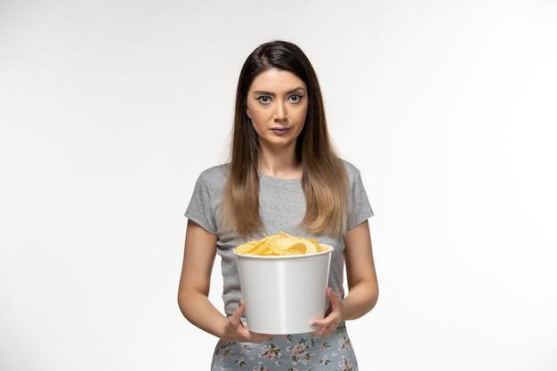 Vorderansicht junge frau, die kartoffelchips beim ansehen des films auf weißer oberfläche hält