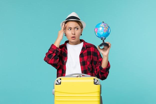 Vorderansicht junge frau, die kleinen globus hält und sich auf reise auf hellblauem raum vorbereitet