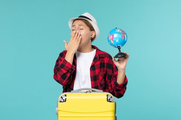 Vorderansicht junge frau, die kleinen globus hält und sich auf reise vorbereitet, der auf blauem raum gähnt