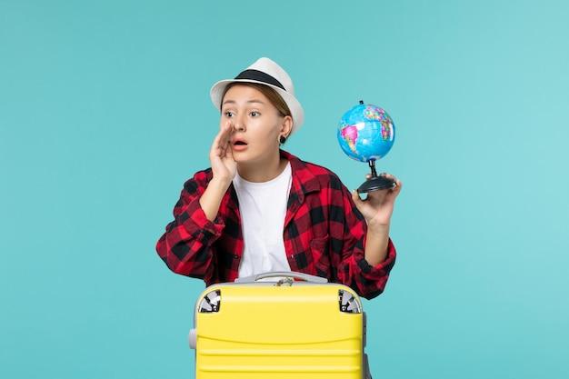 Vorderansicht junge frau, die kleinen globus hält und sich auf reise vorbereitet, die jemanden auf blauem raum anruft