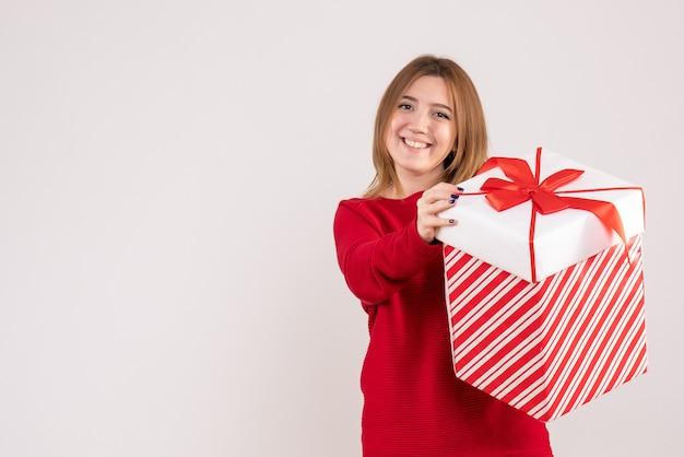 Vorderansicht junge frau, die mit geschenkbox in ihren händen steht