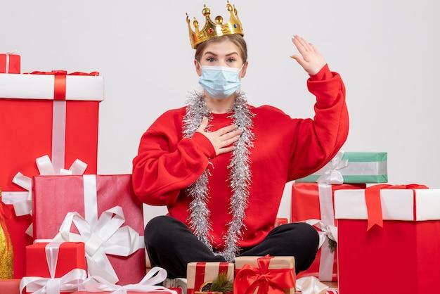 Vorderansicht junge frau, die mit weihnachtsgeschenken in maske und krone sitzt