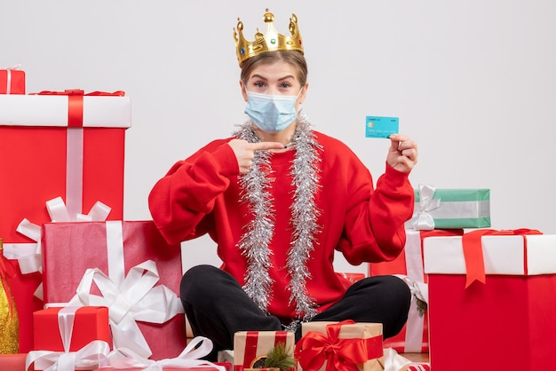 Vorderansicht junge frau, die mit weihnachtsgeschenken sitzt, die bankkarte halten