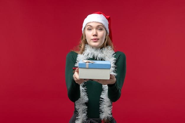 Vorderansicht junge frau, die neujahrsgeschenk auf rotem hintergrund hält