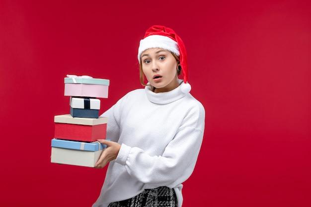 Vorderansicht junge frau, die neujahrsgeschenke auf hellrotem hintergrund hält