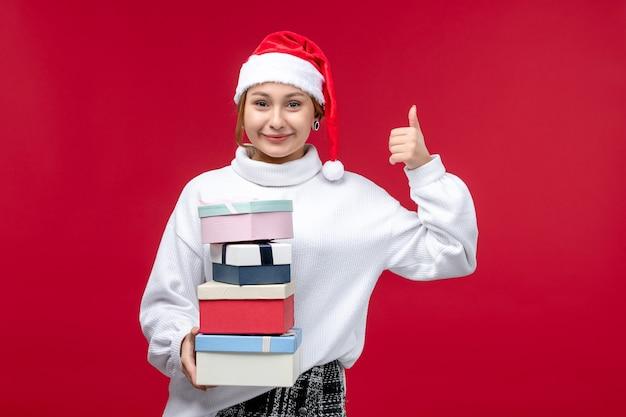 Vorderansicht junge frau, die neujahrsgeschenke auf rotem hintergrund hält