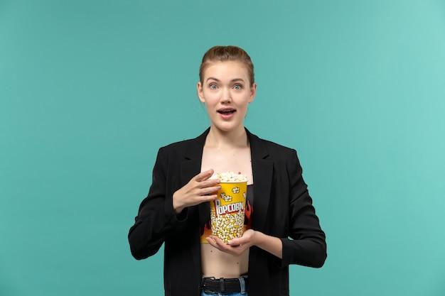 Vorderansicht junge frau, die popcorn hält und film auf der blauen oberfläche sieht