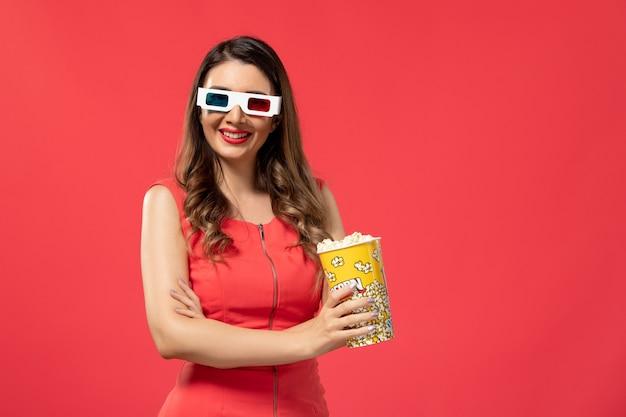 Vorderansicht junge frau, die popcorn in d sonnenbrille auf dem roten schreibtisch hält