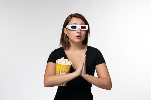 Vorderansicht junge frau, die popcorn in d sonnenbrille hält, die auf weißer oberfläche betet