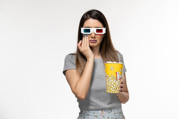 Vorderansicht junge frau, die popcorn isst und film in d sonnenbrille auf der hellen weißen oberfläche sieht