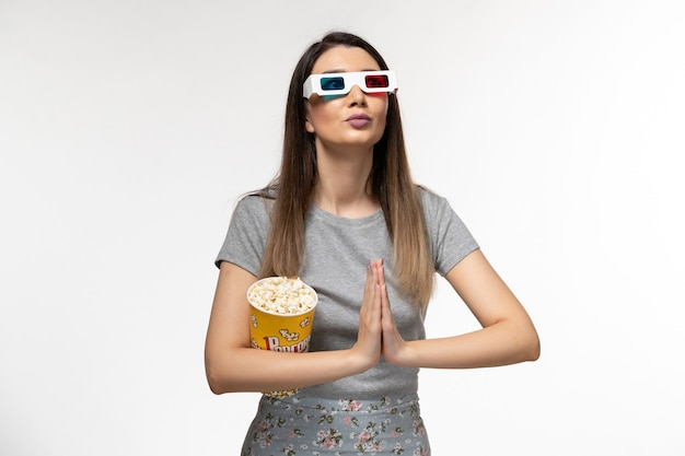 Vorderansicht junge frau, die popcorn isst und film in d sonnenbrille auf weißem schreibtisch sieht