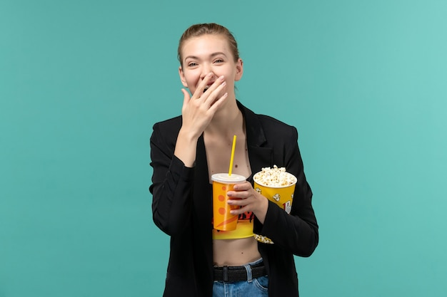 Vorderansicht junge frau, die popcorn mit getränk und film auf der hellblauen oberfläche hält