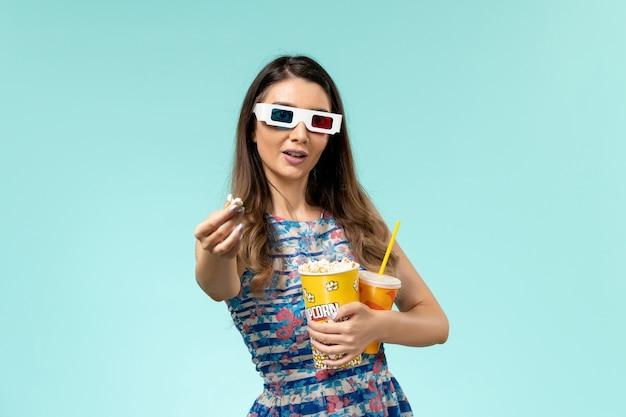 Vorderansicht junge frau, die popcorn-paket hält und in d sonnenbrille auf der blauen oberfläche trinkt