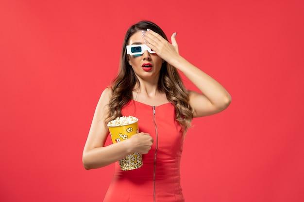 Vorderansicht junge frau, die popcorn-paket in d sonnenbrille auf dem roten schreibtisch hält