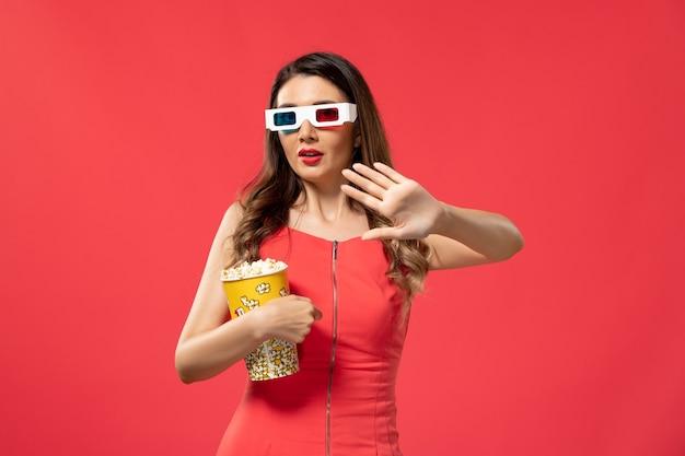 Vorderansicht junge frau, die popcorn-paket in d sonnenbrille auf der roten oberfläche hält