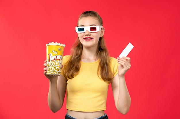 Vorderansicht junge frau, die popcorn-paket und ticket in d sonnenbrille auf hellrotem wandtheater-filmkino-film hält