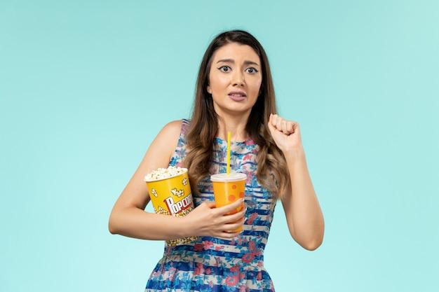 Vorderansicht junge frau, die popcorn und getränk auf dem blauen schreibtisch hält
