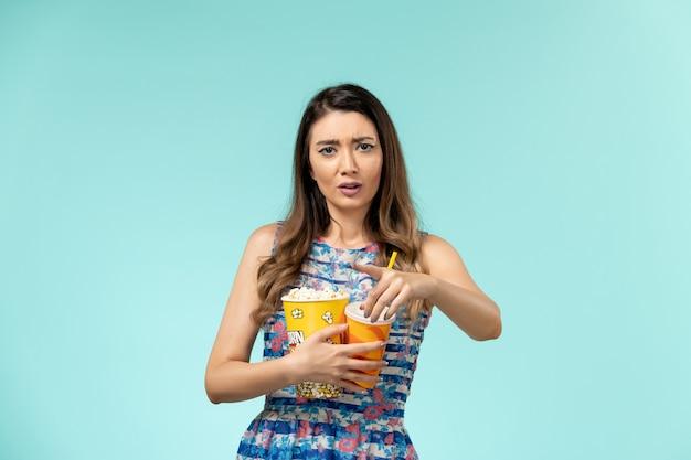 Vorderansicht junge frau, die popcorngetränk hält und film auf blauem schreibtisch sieht