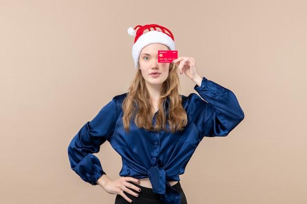 Vorderansicht junge frau, die rote bankkarte auf rosa hintergrundfeiertagen weihnachtsgeldfoto neujahrsgefühl hält