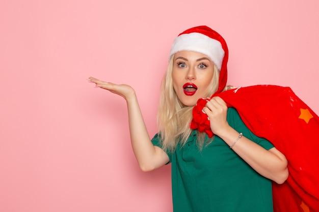 Vorderansicht junge frau, die rote tasche mit geschenken auf rosa wandfeiertagsmodell weihnachten neujahrsfarbfoto santa trägt