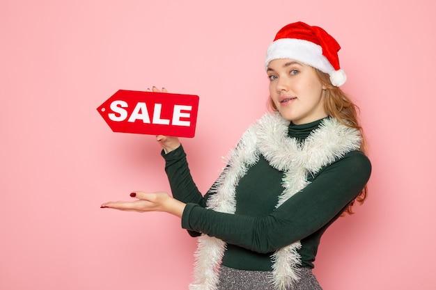 Vorderansicht junge frau, die roten verkaufsschreiben auf rosa wandweihnachtsfeiertagsfotoeinkaufs-mode-emotion hält