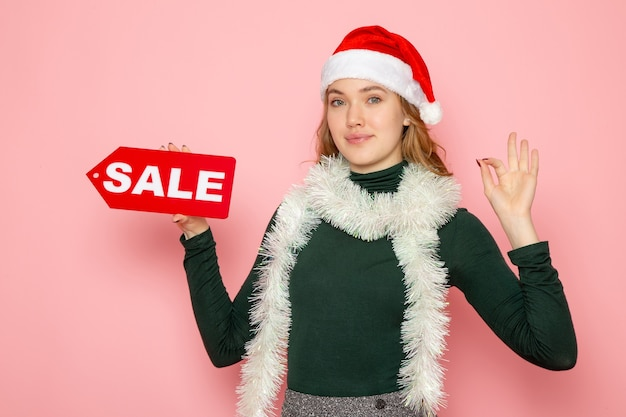 Vorderansicht junge frau, die rotes verkaufsschreiben auf rosa wandfeiertagsfotoeinkaufs-mode-emotion hält
