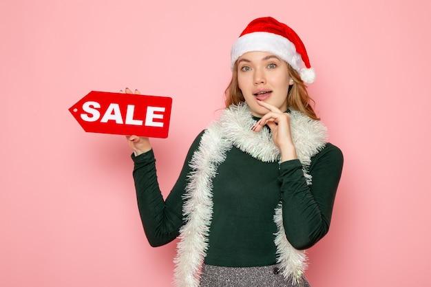 Vorderansicht junge frau, die rotes verkaufsschreiben auf rosa wandweihnachtsferien-neujahrsfoto-mode-emotion hält