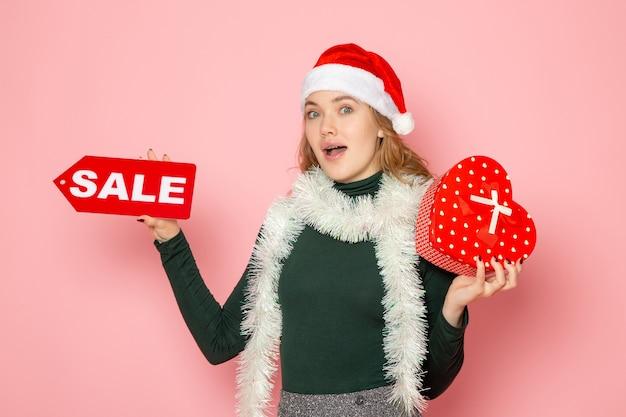 Vorderansicht junge frau, die rotes verkaufsschreiben hält und auf rosa wandweihnachtsjahr-neujahrseinkaufsfeiertagsgeschenk präsentiert