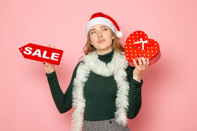 Vorderansicht junge frau, die rotes verkaufsschreiben und geschenk auf rosa wandweihnachts-neujahrseinkaufsgefühle-feiertagsfarbe hält