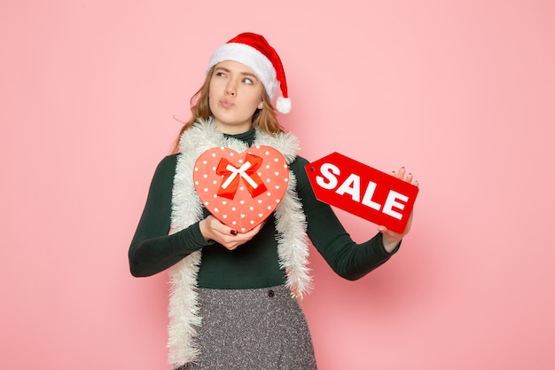 Vorderansicht junge frau, die rotes verkaufsschreiben und geschenk auf rosa wandweihnachts-neujahrseinkaufsmode-emotionsferien hält
