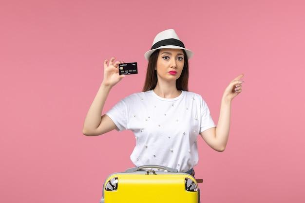 Vorderansicht junge frau, die schwarze bankkarte auf dem rosafarbenen wandreise-farbreisesommer hält