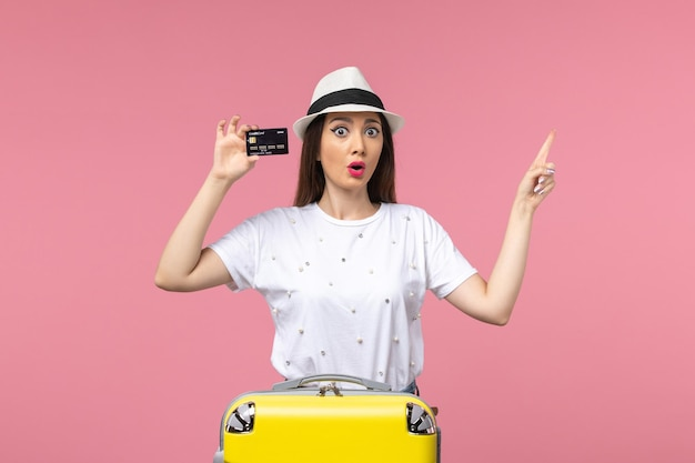 Vorderansicht junge frau, die schwarze bankkarte auf dem rosafarbenen wandreise-reisesommer hält
