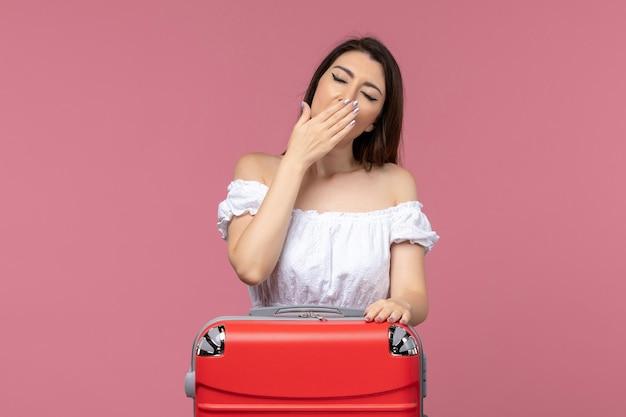 Vorderansicht junge frau, die sich auf urlaub mit ihrer großen tasche vorbereitet, die auf rosa hintergrund im ausland seereise reise reise reise gähnt