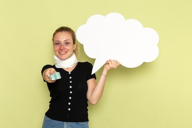 Vorderansicht junge frau, die sich sehr krank und krank fühlt, die großes weißes schild hält, das pillen auf der gesundheitskrankheit der grünen wandkrankheitsmedizin hält
