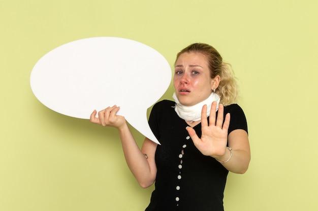 Vorderansicht junge frau, die sich sehr krank und krank fühlt, die großes weißes zeichen hält, das auf der grünen wandkrankheitsmedizin-krankheitsgesundheit aufwirft