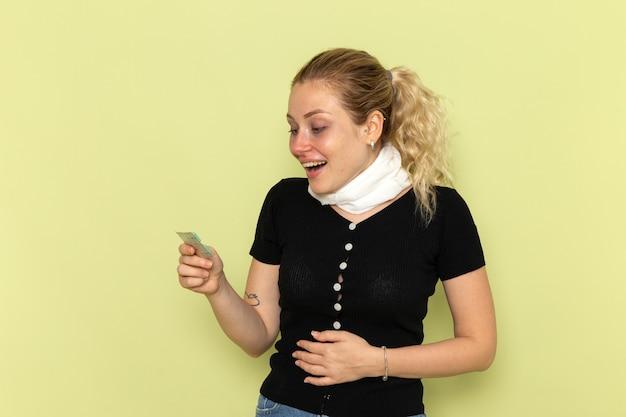 Vorderansicht junge frau, die sich sehr krank und krank fühlt, hält pillen auf der grünen wandkrankheit weibliche medizinkrankheit