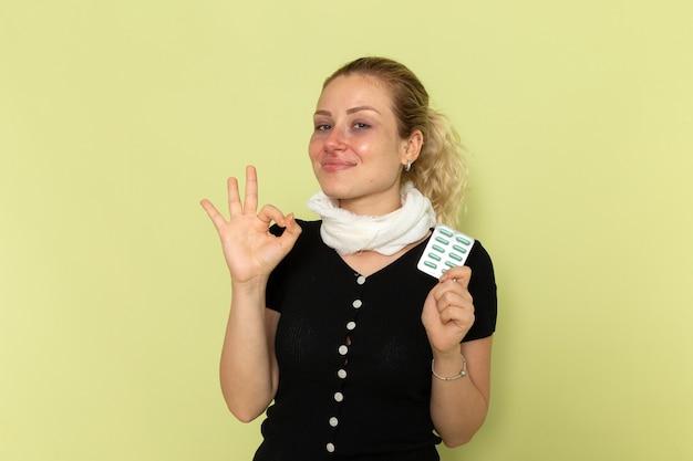 Vorderansicht junge frau, die sich sehr krank und krank fühlt, hält pillen auf der grünen wandkrankheitsmedizinkrankheit