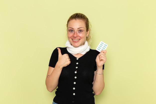 Vorderansicht junge frau, die sich sehr krank und krank fühlt, hält pillen mit lächeln auf der grünen wandkrankheit weibliche medizinkrankheit