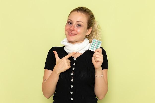 Vorderansicht junge frau, die sich sehr krank und krank fühlt, hält pillen mit leichtem lächeln auf der grünen wandkrankheit weibliche medizinkrankheit